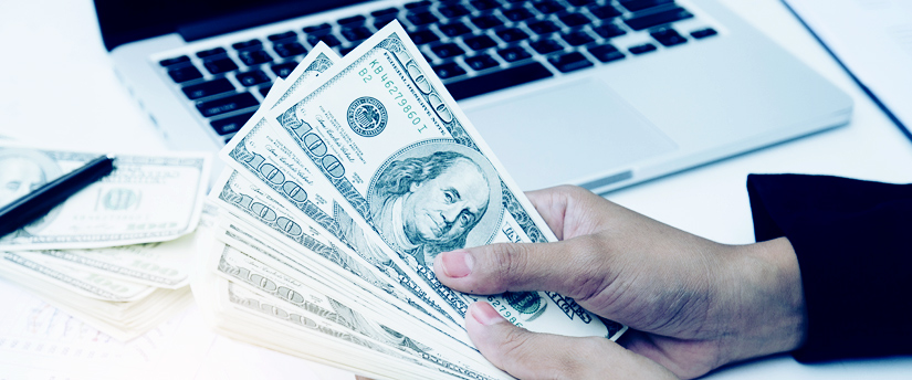 a man's hands holding dollar banknotes with some more banknotes on the side in front of an open laptop
