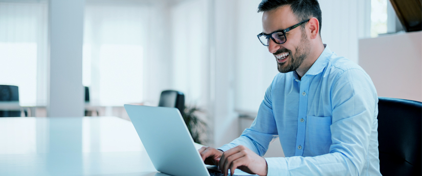 a man wearing glasses and working on his laptop, depicting affiliates and working on affiliate businesses